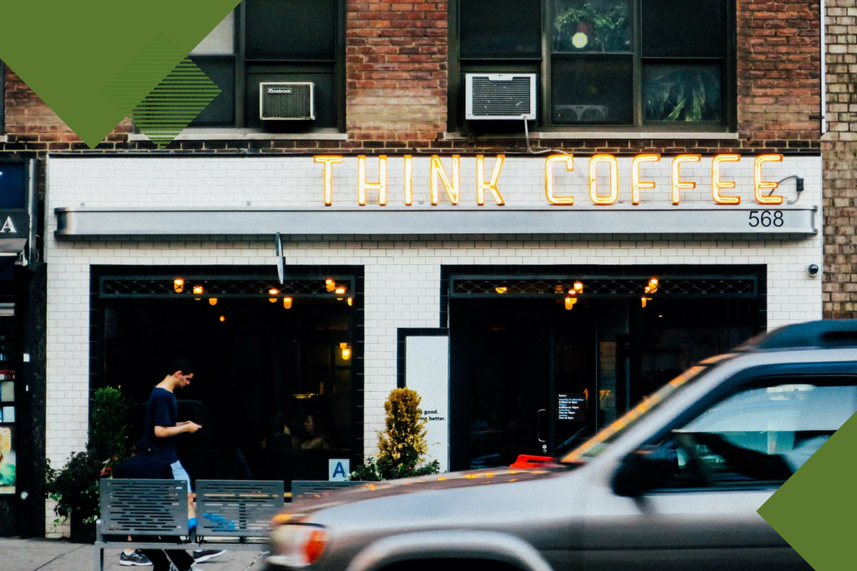 "Man on phone walking past coffee shop called ""think coffee"" with dark green geometric shapes on top"