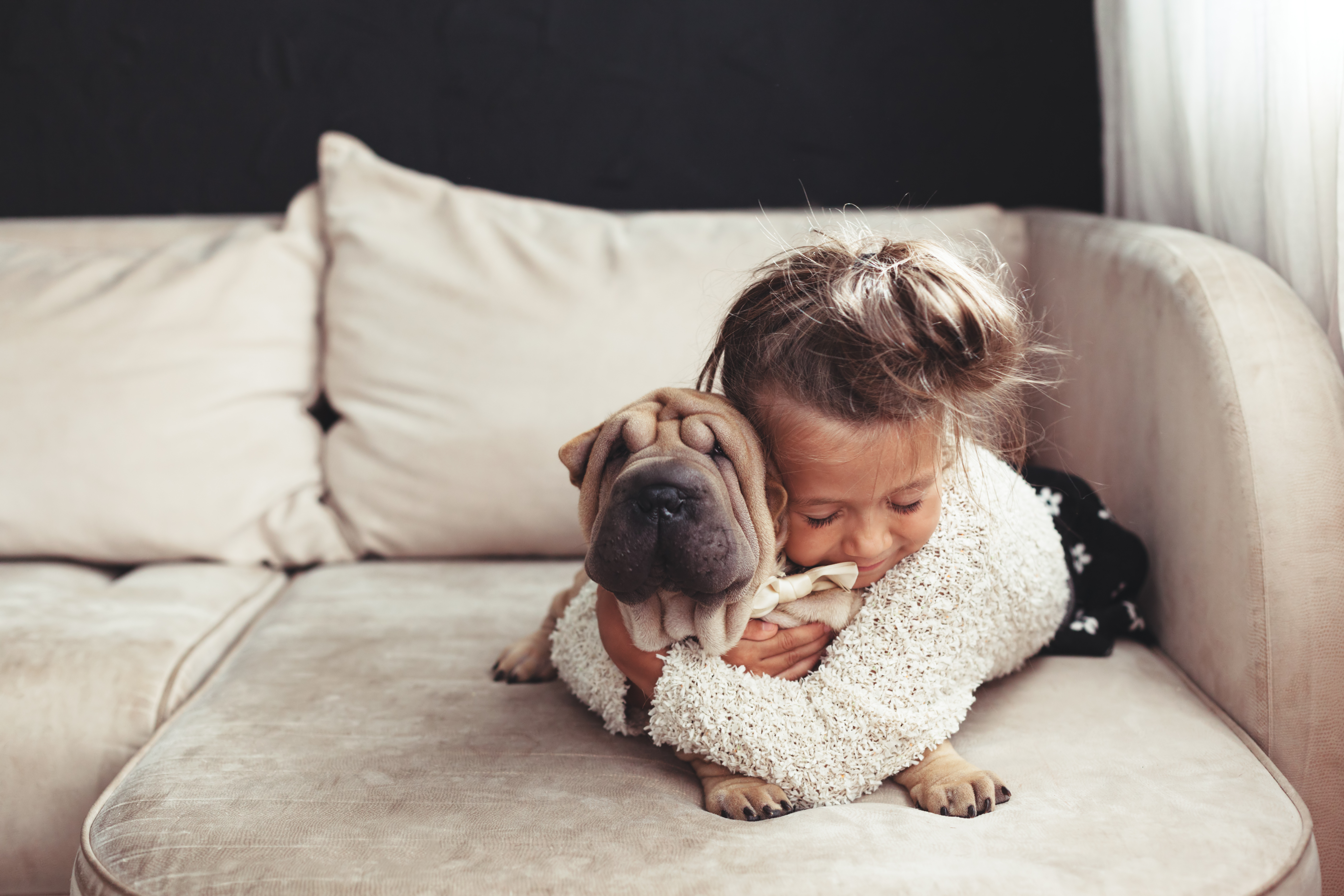 little girl cuddling with dog
