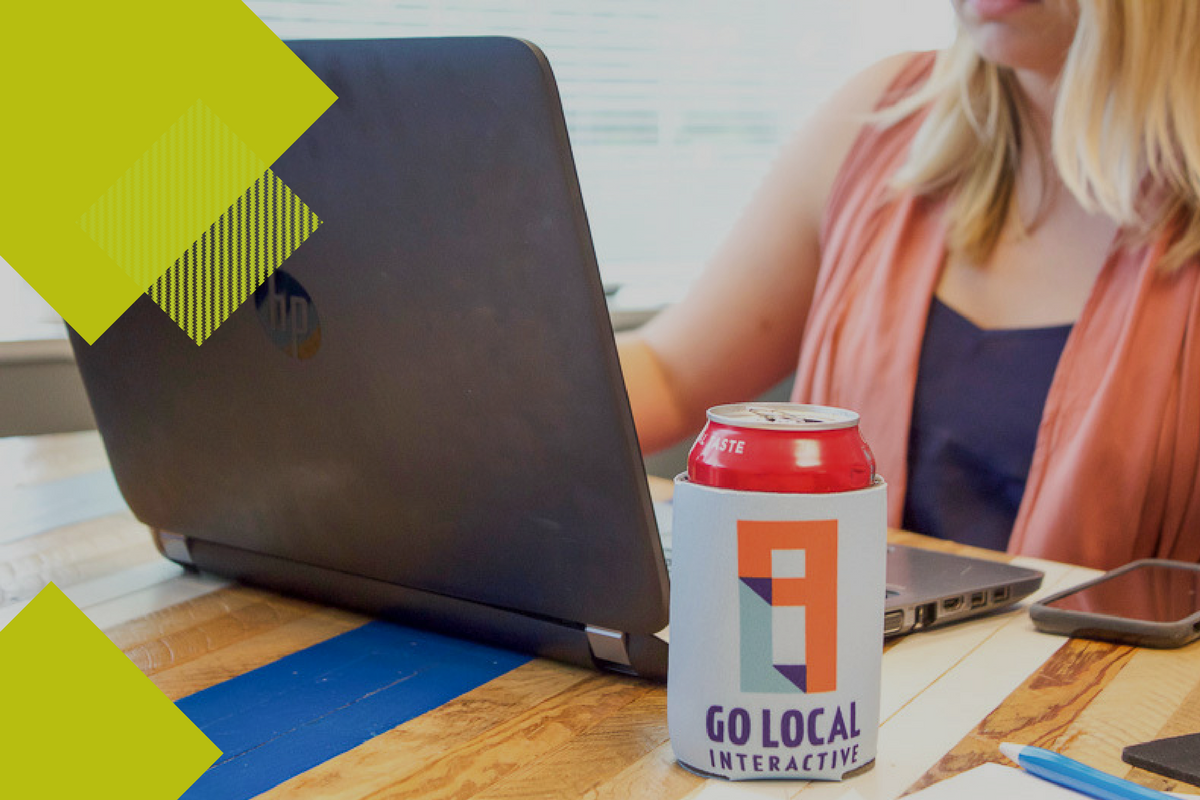 girl looking at computer with soda can and Go Local Interactive koozie